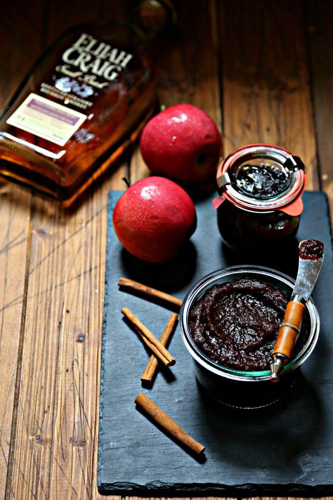 2 jars of apple butter on black slate. Apples, bourbon bottle and cinnamon sticks surrounding.