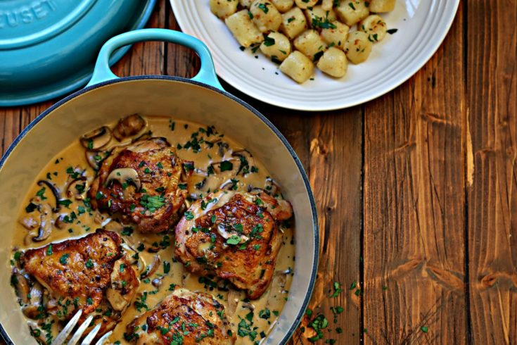 chicken with cream sauce in blue pot. White bowl of gnocchi to side.