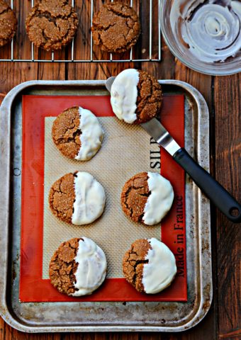 cookies dipped in white chocolate on baking sheet.
