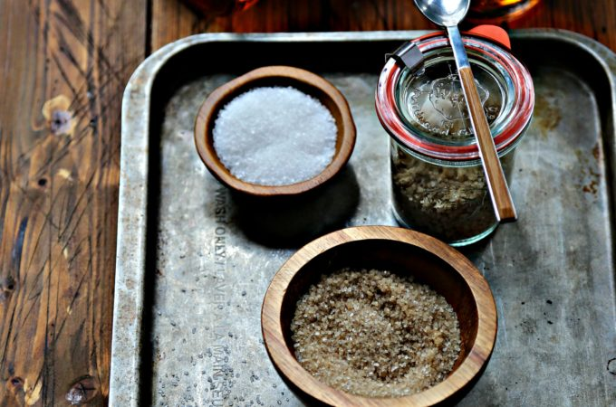 two bowls of salt, one glass jar of bourbon salt with spoon on baking sheet.