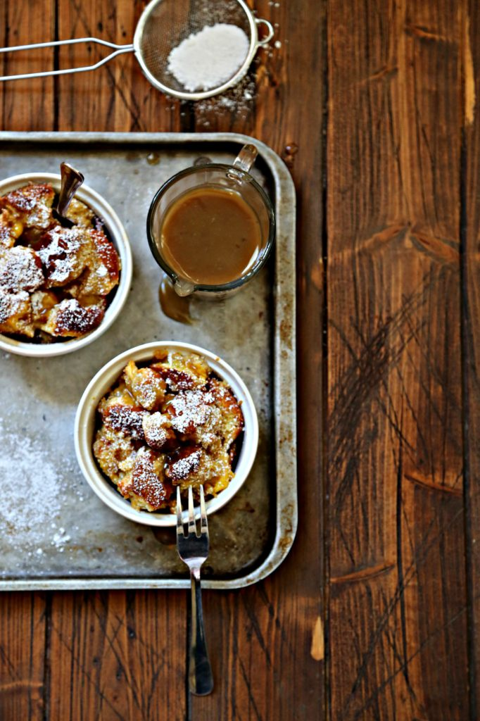 2 ramekins of bread pudding on baking sheet with pitcher of sauce.