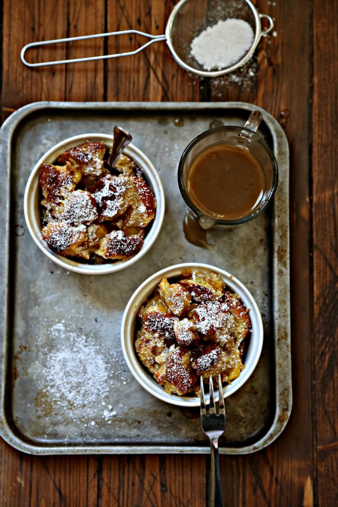 bread puddings on baking sheet with pitcher of sauce.