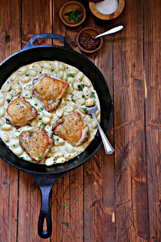 skillet with chicken and gnocchi. Wood bowl of mustard behind.