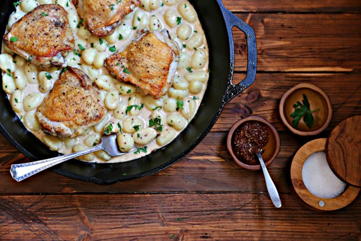 chicken in skillet with gnocchi. Bowl of mustard, parsley and salt to side.