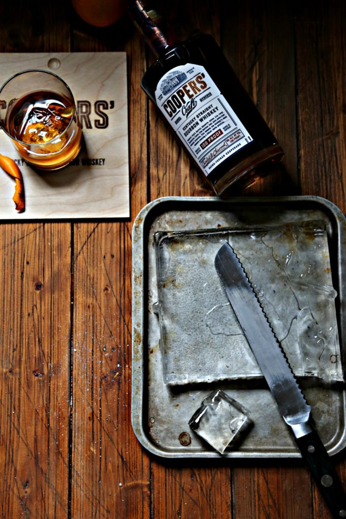 old fashioned cocktail, bottle of bourbon, baking sheet with clear ice and knife.