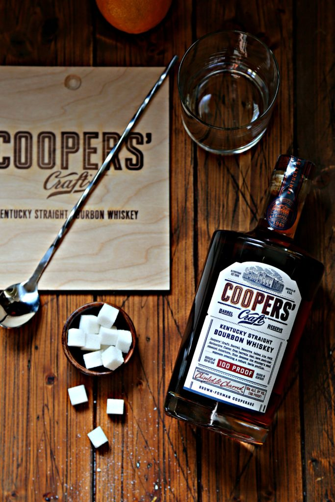 sugar cubes in brown bowl, bottle of bourbon, glass and stirring spoon.