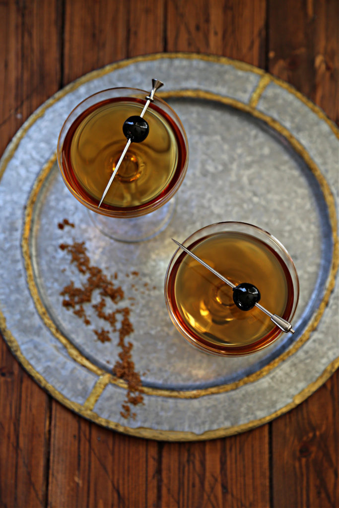 two cocktails with cherry garnish on silver plate