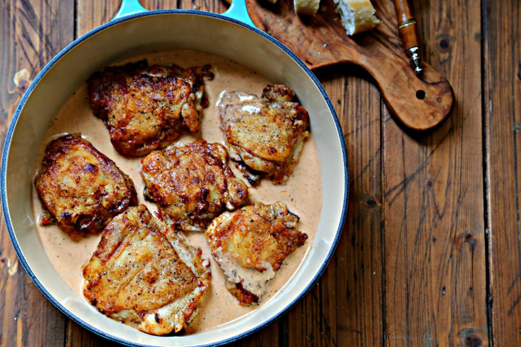 chicken with sauce in blue skillet. Board with bread and butter behind.