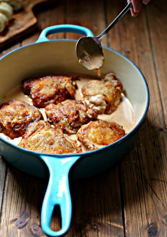 chicken thighs in sauce in blue skillet. Spoon dipping into sauce.