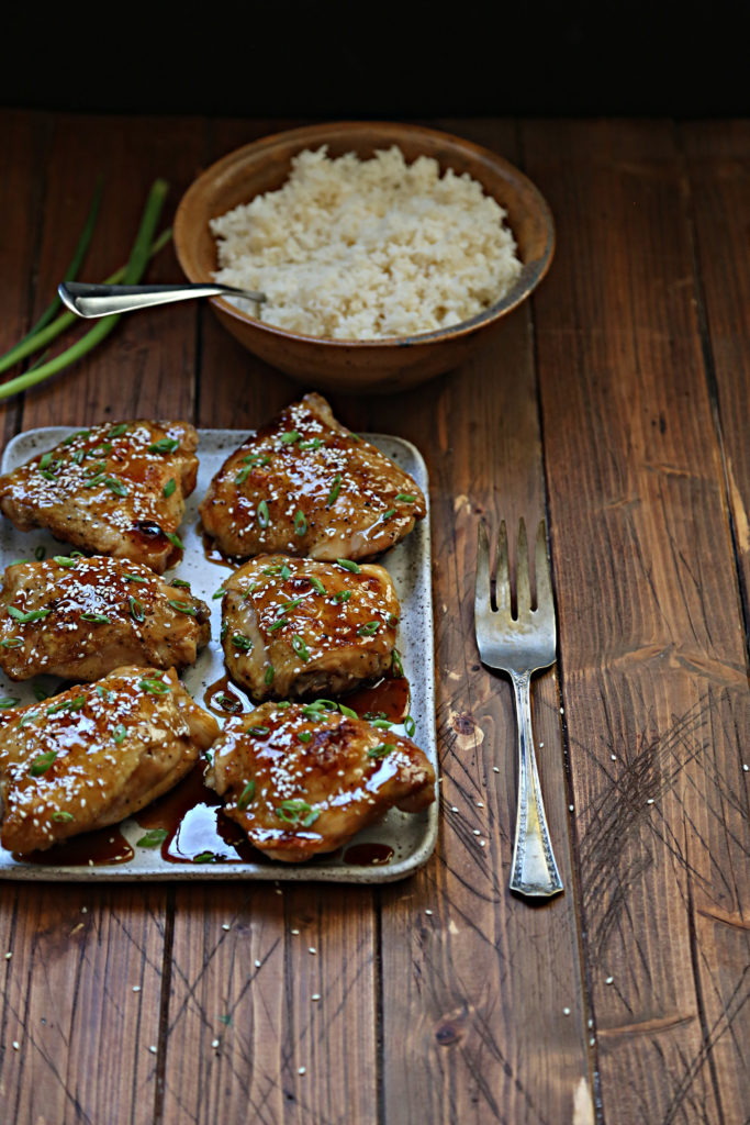 Chicken thighs on platter. Bowl of rice behind with spoon. Serving fork to side.