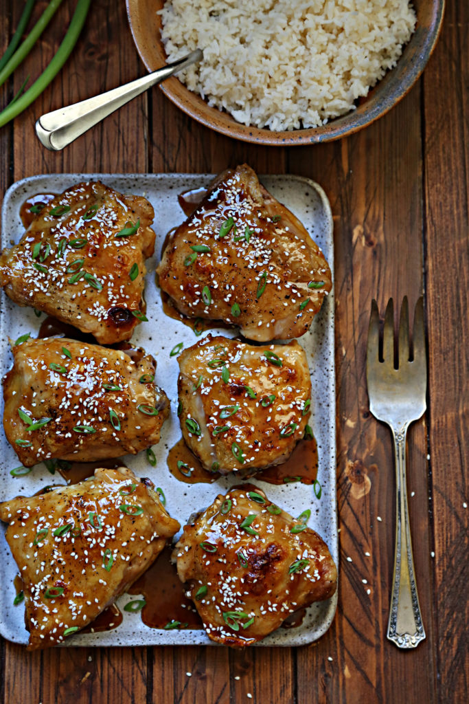 chicken thighs on platter, serving fork to side. Bowl of rice behind.