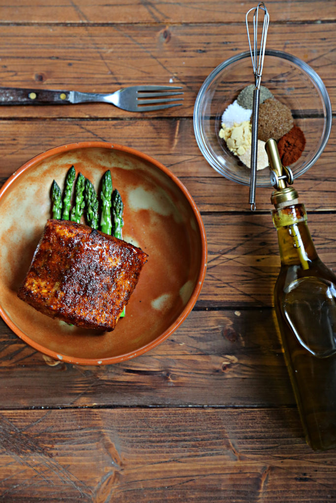 fork, small glass bowl of spices and olive oil jar. Brown bowl of salmon a top asparagus.