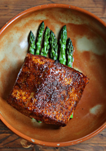 salmon over asparagus in brown bowl.
