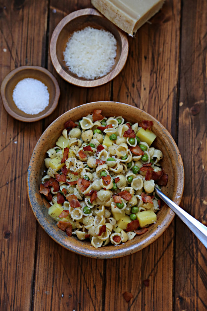 brown bowl with shells pasta peas and bacon. Small bowls of cheese and salt in background.