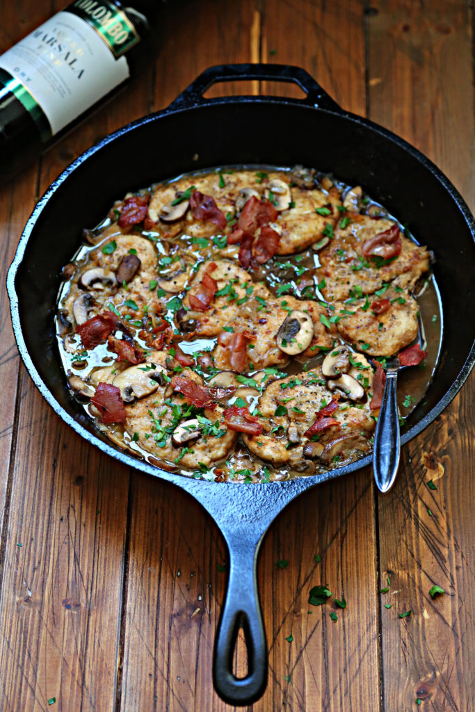 homemade chicken marsala recipe in cast iron skillet and brown wooden background