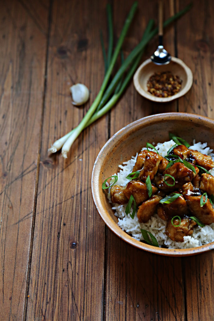 brown bowl with rice and orange chicken. Small brown bowl with spice and spoon, green onions in background.