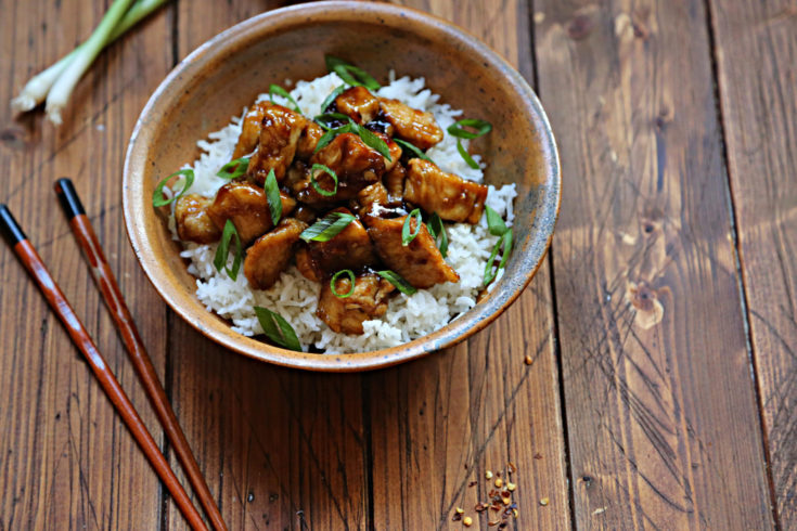 brown bowl with rice and orange chicken. Chopsticks to side.