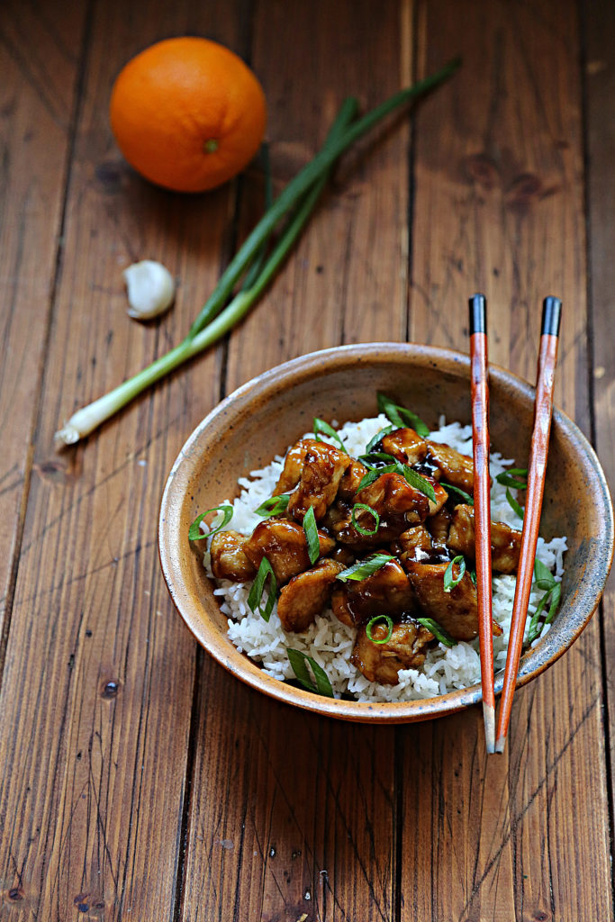 brown bowl with rice and orange chicken. Chopsticks resting on bowl. Orange, garlic and green onion in background.