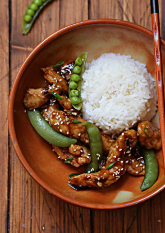 brown bowl with rice, lemon chicken, sugar snap peas