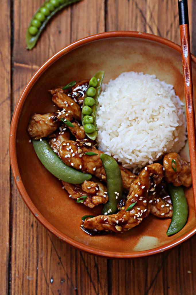 brown bowl with rice, lemon chicken, sugar snap peas