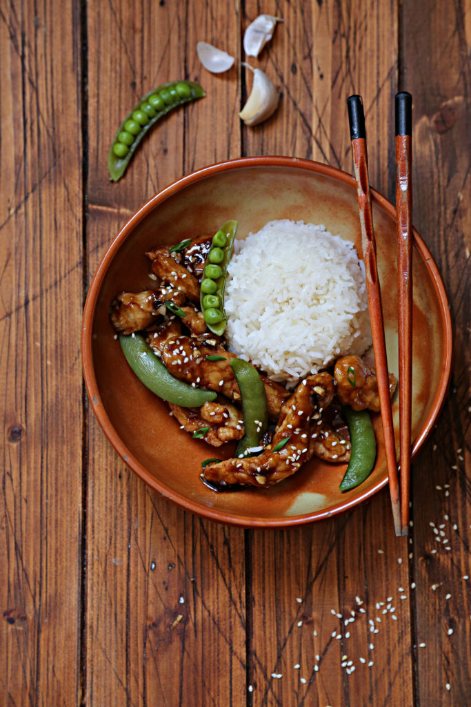 brown bowl with strips of lemon chicken, snap peas and rice. Chopsticks resting on bowl.