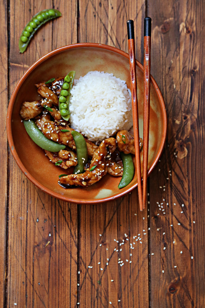 brown bowl with lemon chicken, snap peas and rice. Chopsticks resting on bowl. Sesame seeds scattered around bowl.