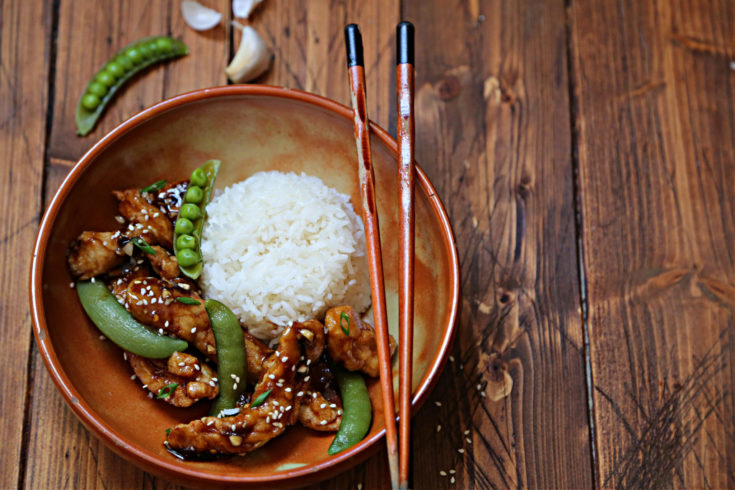 brown bowl with rice, lemon chicken, snap peas and chopsticks. Garlic and snap peas scattered around bowl.