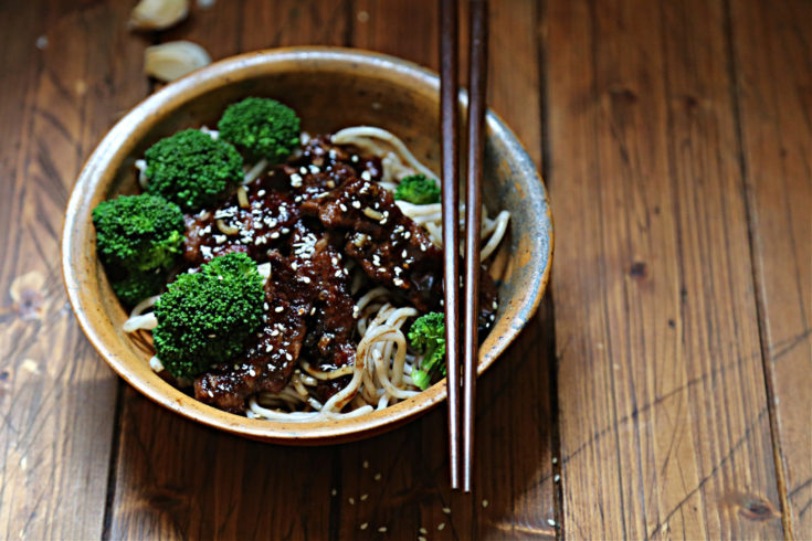 brown bowl with noodles broccoli and beef teriyaki. Chopsticks resting on bowl. Garlic cloves behind bowl.