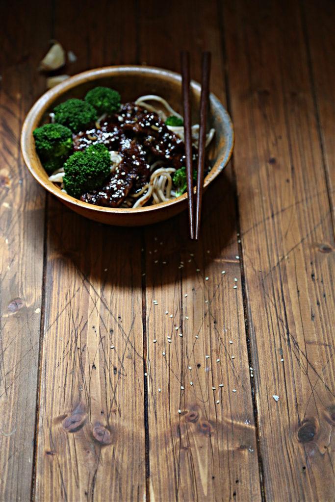 bowl of teriyaki beef and broccoli. Chopsticks resting on bowl. Sesame seeds scattered around.
