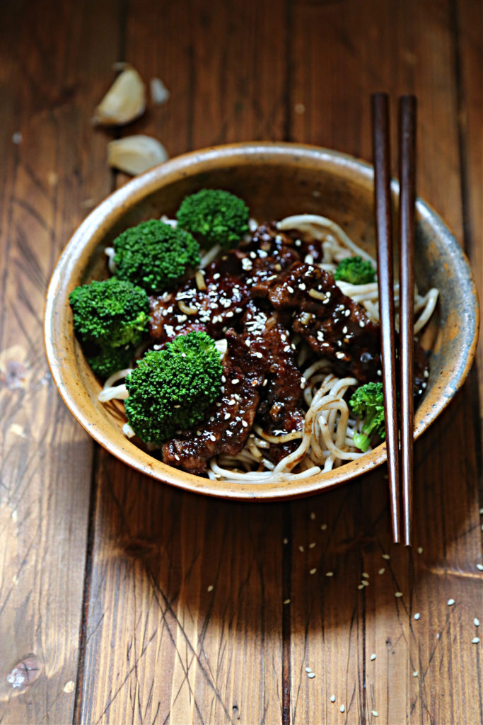 bowl of teriyaki beef and broccoli with noodles. Chopsticks to side of bowl.