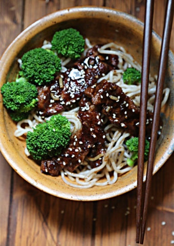 brown bowl with broccoli noodles and beef teriyaki. Chopsticks resting on bowl.
