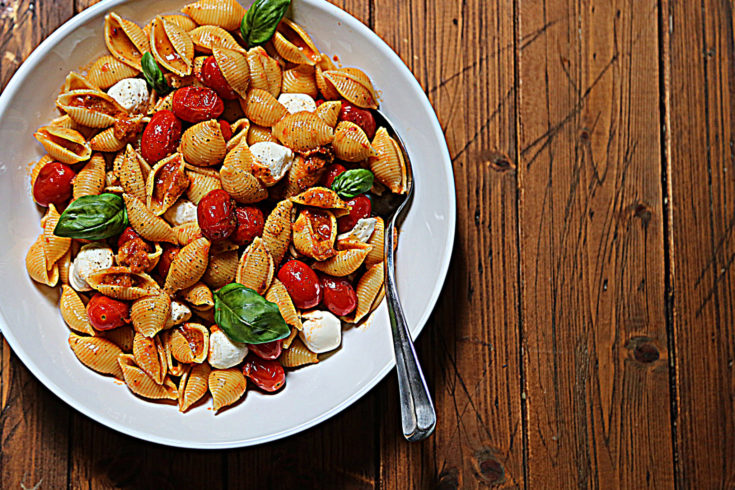 white bowl of pasta salad with serving spoon.