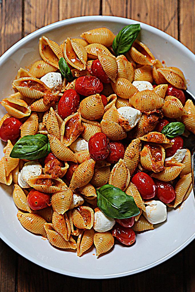 close up of white bowl of pesto pasta salad