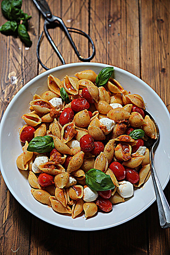 white bowl with pasta shells, tomatoes, basil and mozzarella balls. Serving spoon in bowl. Scissors and basil surrounding.