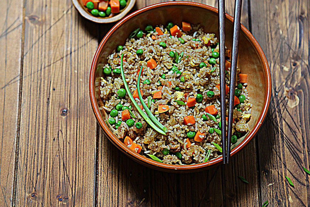 brown bowl of fried rice with chop sticks.