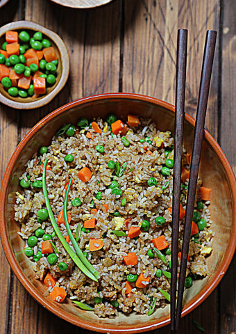 fried rice in brown bowl with chopsticks. Small bowl of vegetable blend to side.