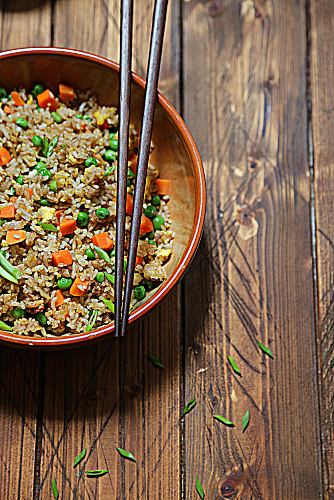 close up view of bowl of vegetable fried rice with chopsticks.