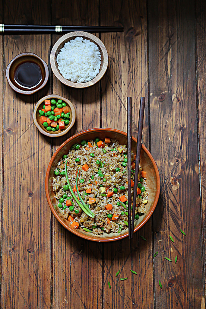 brown bowl of fried rice with chop sticks. Small bowls of rice, soy sauce and vegetables in background.