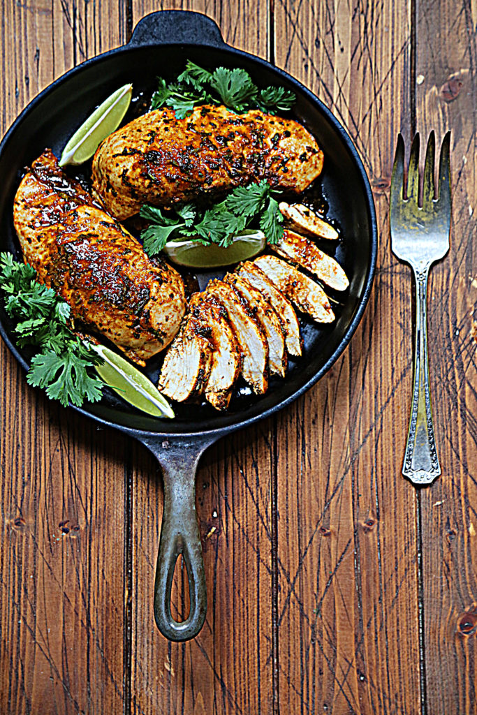 black skillet with 2 whole chicken breasts, 1 sliced. Lime wedges and cilantro scattered. Fork to side of skillet.