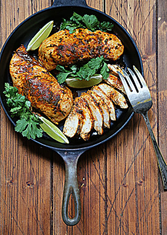 2 cooked chicken breasts, 1 sliced with scattered cilantro and lime wedges in black skillet. Fork resting on side.