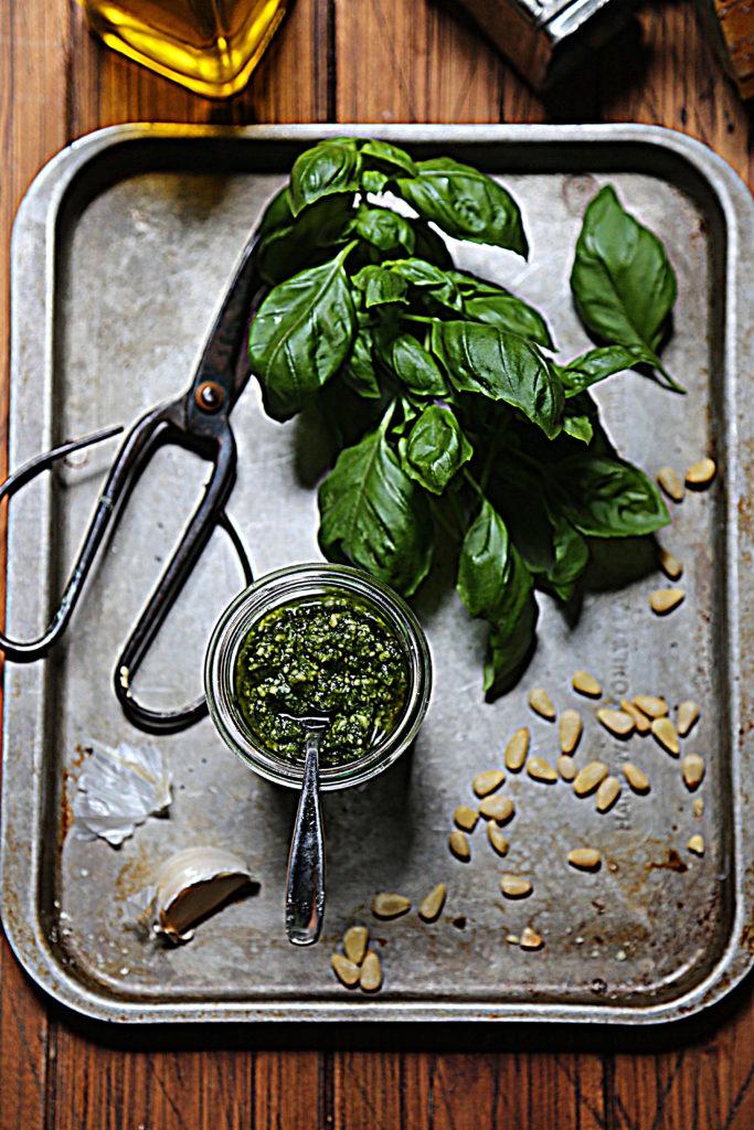 basil, scissors, pine nuts, garlic clove and glass jar of pesto on baking sheet.