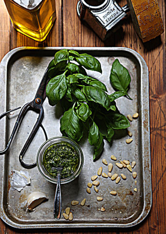 pesto in jar with spoon on baking sheet with basil, pine nuts, scissors and garlic cloves. Glass jar of olive oil and cheese grater in background.