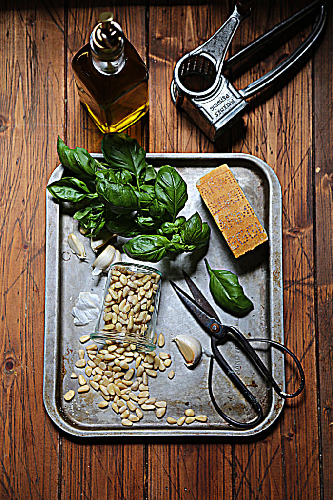 baking sheet with basil, pine nuts in glass jar, garlic cloves, scissors, cheese wedge. Olive oil and cheese grater in background.