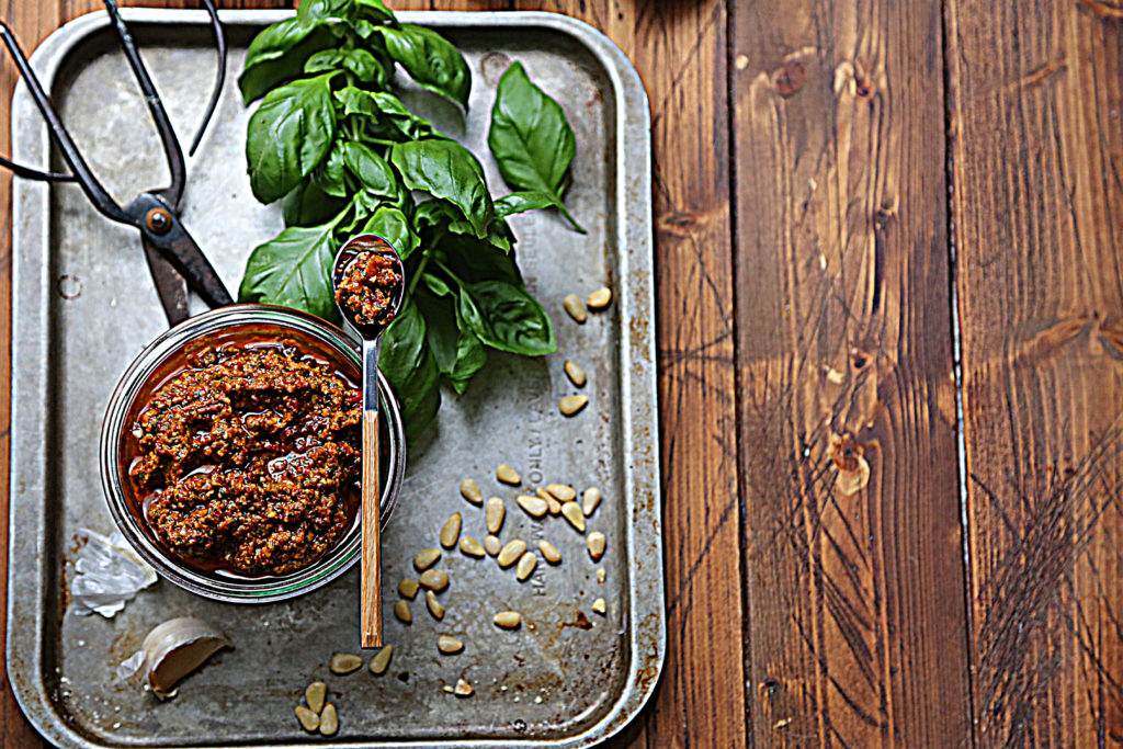 red pesto in glass jar on baking sheet with basil, pine nuts and scissors.