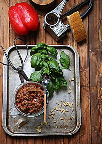 baking sheet with jar of red pesto and spoon. Basil, pine nuts and scissors on baking sheet. Red bell pepper and cheese grater in background.