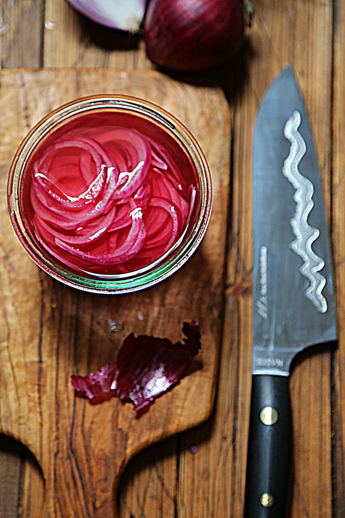 jar of pickled red onions. Onion peel and knife surrounding.