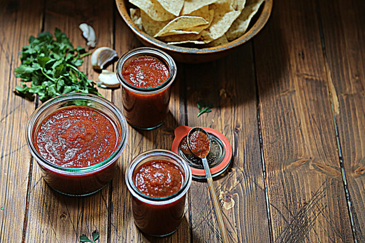three glass jars of red salsa. Bowl of chips, garlic cloves and cilantro surrounding.