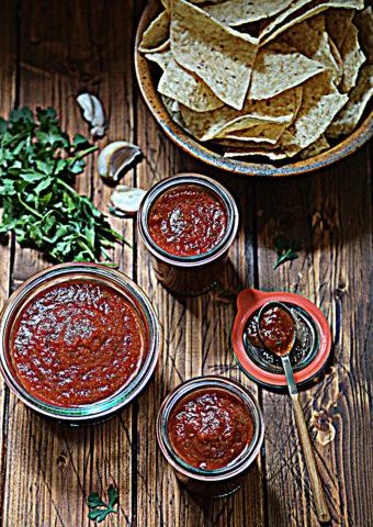3 jars of red salsa. Chips, cilantro and garlic cloves around.