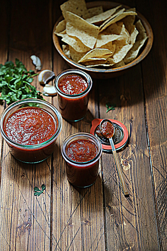 3 small glass jars of red salsa. Bowl of chips, cilantro and garlic cloves behind jars.