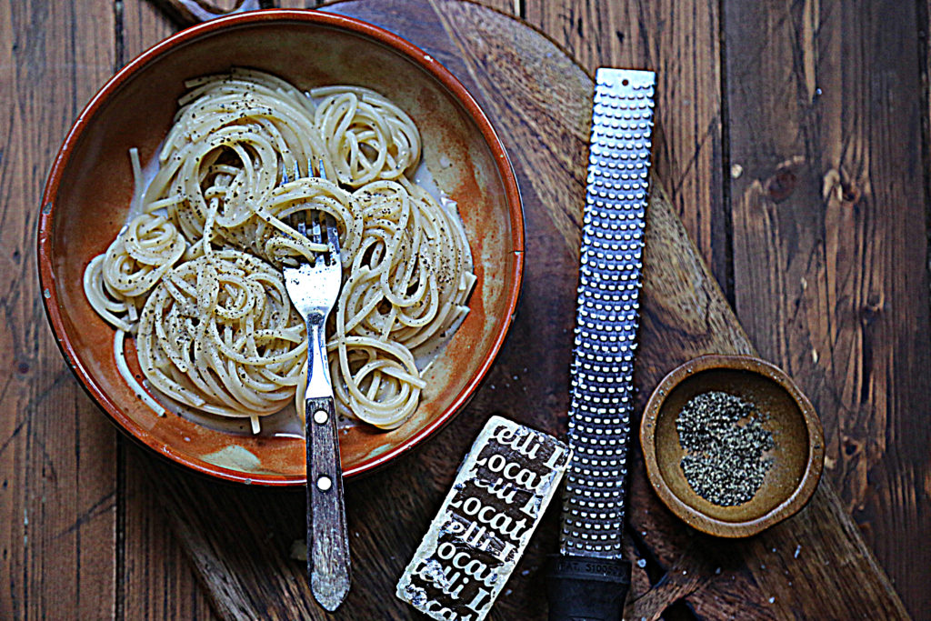 bowl of cacio e pepe pasta with fork. Bowl of pepper, microplane and wedge of Pecorino cheese to side.